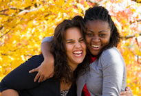 Two female students hug in front of fall folliage.