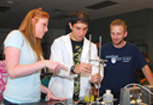 Three students, two men and one woman, work together in an engineering lab.