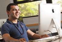 A male Penn State Greater Allegheny undergraduate student smiles and works on a computer.